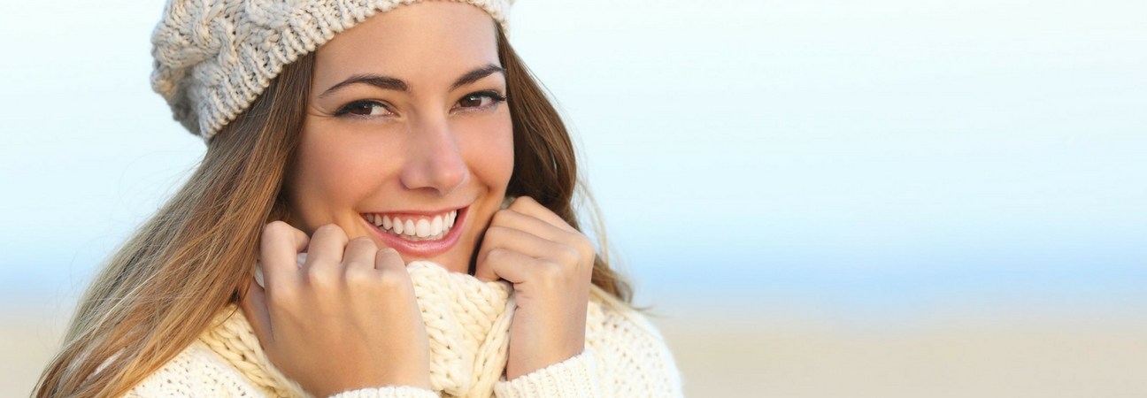 woman in a sweater showing off her teeth whitening results