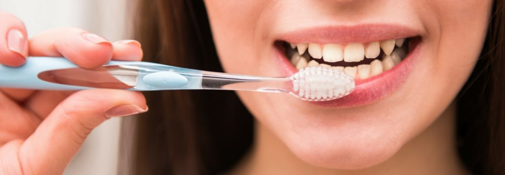 woman brushing her teeth as part of oral systemic health